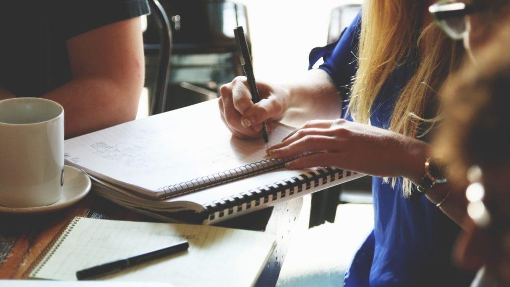 Hand hält Stift und Papier