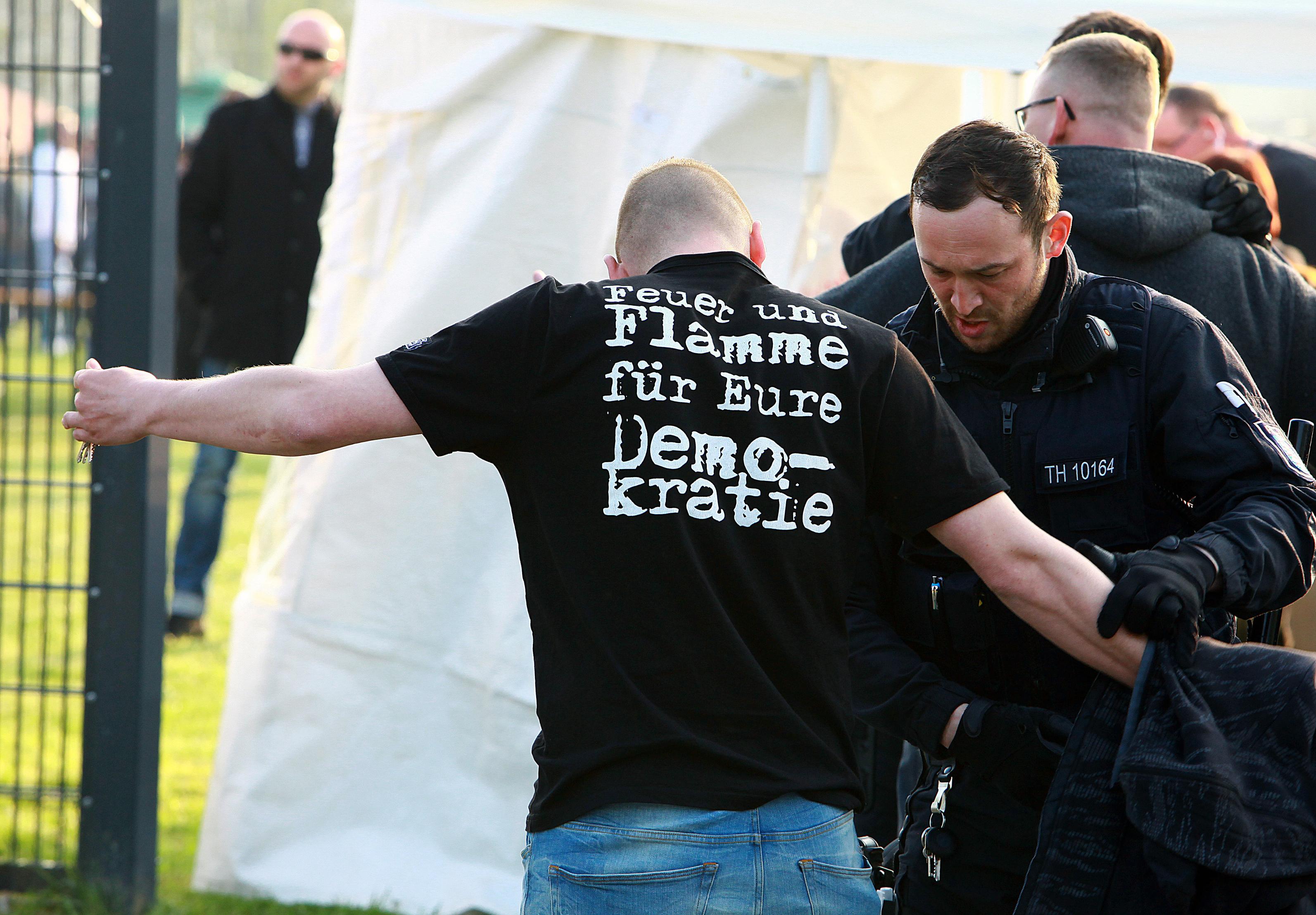 Polizist durchsucht Teilnehmer bei rechtsRock-Konzert