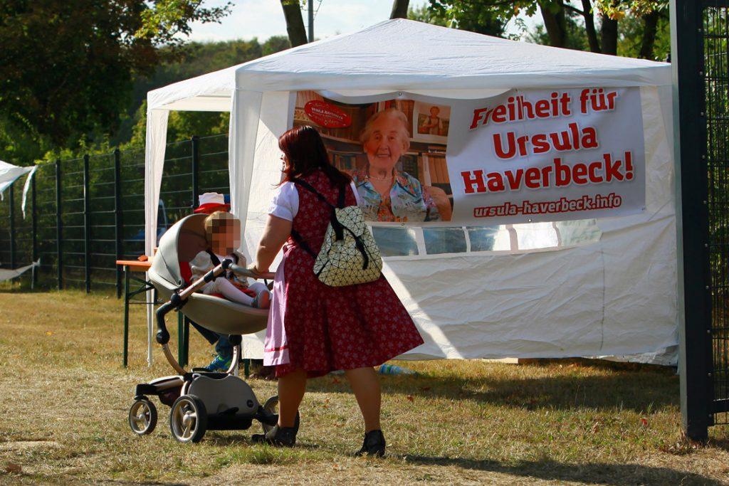 Rechtsextreme Besucherin des Eichsfeldtages mit ihrem Kleinkind - im Hintergrund ein Banner auf dem Freiheit für die Holocaustleugnerin Ursula Haverbeck gefordert wird.